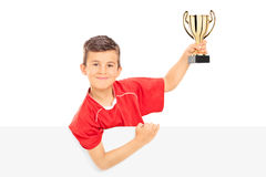 Junior athlete holding a trophy behind a panel royalty free stock images