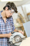 Junior carpenter using circular saw. Junior carpenter using a circular saw Stock Image