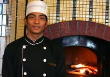 Junior chef at pizza restaurant. Junior chef at front of pizza oven stock photography