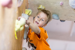 Junior Climber getting the hold on climbing wall Royalty Free Stock Photo