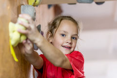 Junior Climber hanging on holds on climbing wall Stock Photography
