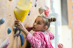 Junior Climber hanging on holds on climbing wall. Junior Climber Girl shirt hanging on holds on climbing wall of indoor gym Stock Image