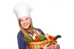 Junior cook holding a basket with vegetables Royalty Free Stock Images