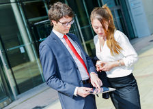 Junior executives consulting a touchpad in front of their company stock photos