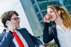 Junior executives having a coffee break in front of their company Stock Photo