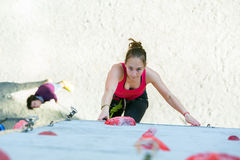 Junior female Athlete on climbing Wall and belaying referee Stock Image