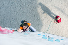 Junior female Athlete on climbing Wall and belaying referee Stock Photography