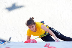 Junior female Athlete makes hard move on climbing wall Stock Photography