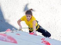 Junior female Athlete makes hard move on climbing wall Royalty Free Stock Image