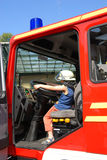 Junior firefighter. Kid playing at steering wheel of fire engine Stock Photography