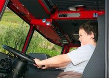 Junior fireman. Young boy pretending to drive a fire truck stock photo