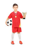 Junior football player holding a golden cup Royalty Free Stock Images
