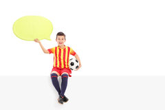 Junior football player holding a speech bubble. Seated on a panel isolated on white background Stock Photos
