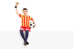 Junior football player holding a trophy on a panel. Isolated on white background Stock Images