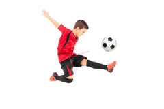 Junior football player kicking a ball. Isolated on white background royalty free stock images