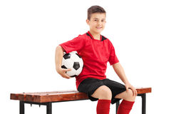 Junior football player posing seated on a bench. Proud junior football player posing seated on a wooden bench and holding a football in his hand isolated on Royalty Free Stock Image