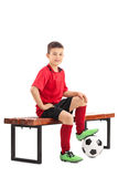Junior football player sitting on a bench stock photo