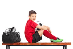 Junior football player sitting on a bench stock photography