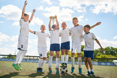Junior Football Team Celebrating Victory. Portrait of junior football team cheering happily and jumping holding trophy cup after winning match Stock Photo