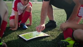 Coach explains game tactic moving figures on scheme. Junior football team coach explains game tactic moving figures on map squatting on pitch close vertical view stock footage