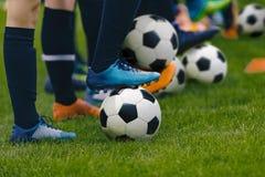 Junior Football Training Session Spieler, die in Folge mit klassischen Schwarzweiss-Bällen stehen stockbild