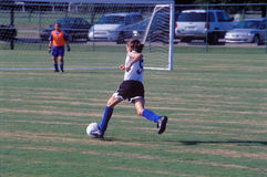 Junior girl soccer  - going for a goal. Girl soccer player heading towards the goal Royalty Free Stock Photos