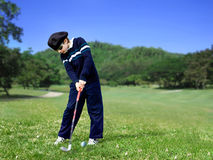 Junior golfer swing. Young junior golfer swinging the ball on a golf course Royalty Free Stock Images