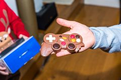 Junior hand holding gift chocolate game console controller.  Stock Photos