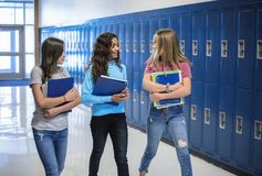 Junior High school Students talking and standing by their locker in a school hallway. Candid photo of Three Junior High school Students talking together in a Royalty Free Stock Image