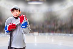 Junior Hockey Player Posing in Arena. Junior hockey player posing on ice in sports arena with hockey stick. Shallow depth of field on background and copy space stock images