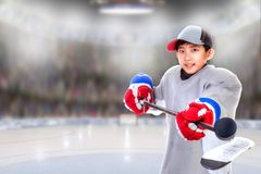 Junior Hockey Player Posing in Arena. Junior hockey player posing on ice in sports arena. Shallow depth of field on background and copy space royalty free stock photo