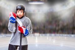 Junior Hockey Player Posing in Arena. Junior hockey player posing on ice in sports arena. Shallow depth of field on background and copy space royalty free stock photos