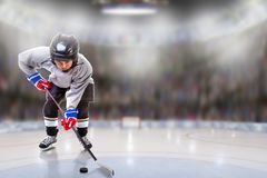 Junior Hockey Player Puck Handling in Arena. Low angle view of hockey player handling puck on ice with sports arena full of fans in the stands and copy space royalty free stock photo