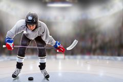 Junior Hockey Player Puck Handling in Arena. Low angle view of hockey player handling puck on ice with sports arena full of fans in the stands and copy space stock photos