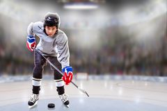 Junior Hockey Player Puck Handling in Arena. Low angle view of hockey player handling puck on ice with sports arena full of fans in the stands and copy space royalty free stock images