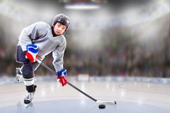 Junior Hockey Player Puck Handling in Arena. Low angle view of hockey player handling puck on ice with sports arena full of fans in the stands and copy space stock photo