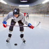 Junior Ice Hockey Player in Crowded Arena. Junior ice hockey player handling puck on ice with arena full of fans in the stands and copy space. 3D rendering of Royalty Free Stock Photo