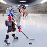 Junior Ice Hockey Player in Crowded Arena. Junior ice hockey player handling puck on ice with arena full of fans in the stands and copy space. 3D rendering of Royalty Free Stock Image