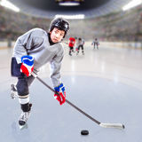 Junior Ice Hockey Player in Crowded Arena. Junior ice hockey player handling and shooting puck on ice with arena full of fans in the stands and copy space. 3D Stock Images