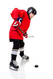 Junior Ice Hockey Player Isolated on White Background. Junior ice hockey player with full equipment and red uniform posing for a shot with a puck. Isolated on Stock Photo