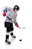 Junior Ice Hockey Player Isolated on White Background. Junior ice hockey player with full equipment and uniform posing for a shot with a puck. Isolated on white Royalty Free Stock Images