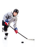 Junior Ice Hockey Player Isolated on White Background. Junior ice hockey player with full equipment and uniform posing for a shot with a puck. Isolated on white royalty free stock photos