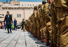 Junior Israeli Defence Force soldiers in uniform pay homage at Jerusalem`s Wailing Wall in the Old City. An ultra-orthodox jewish stock images