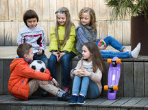 Junior kids chatting outdoor. Group of cheerful lsmiling junior school children chatting outdoors Royalty Free Stock Photos