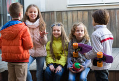 Junior kids chatting outdoor. Group of smiling junior school children chatting outdoors Royalty Free Stock Image