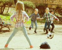 Junior kids playing street football outdoors. In spring day Royalty Free Stock Photo