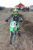 Junior motorbike rider posing on motorbike. Royalty Free Stock Images