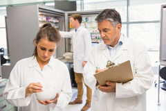Junior pharmacist mixing a medicine being supervised Stock Photography