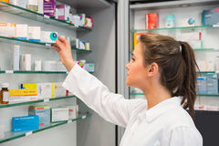 Junior pharmacist taking medicine from shelf Stock Photo