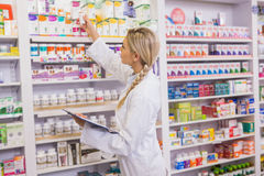 Junior pharmacist taking medicine from shelf Stock Photography
